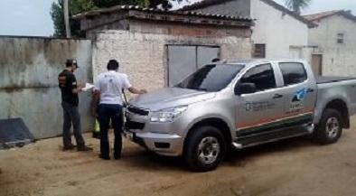 Fotografia de um carro da Semace em frente a um dos locais autuados. Ao lado do carro estão um fiscal folheando alguns papéis e um homem de blusa branca
