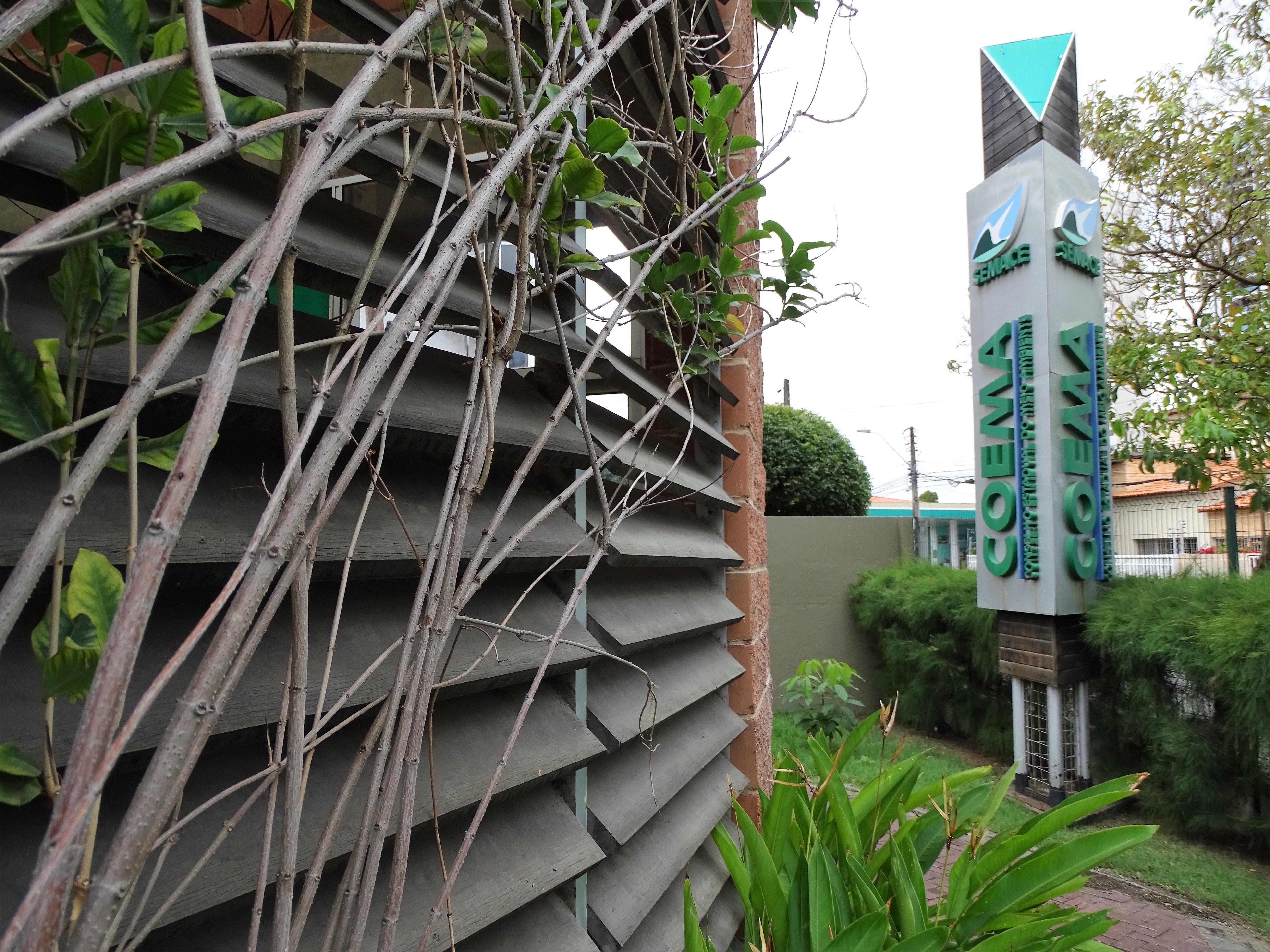 Fotografia da fachada do Coema. Em primeiro plano, à esquerda, está uma parede com venezianas de madeira coberta por galhos e folhas. À direita, um letreiro vertical apresenta o seguinte texto na cor verde: Semace. Coema.