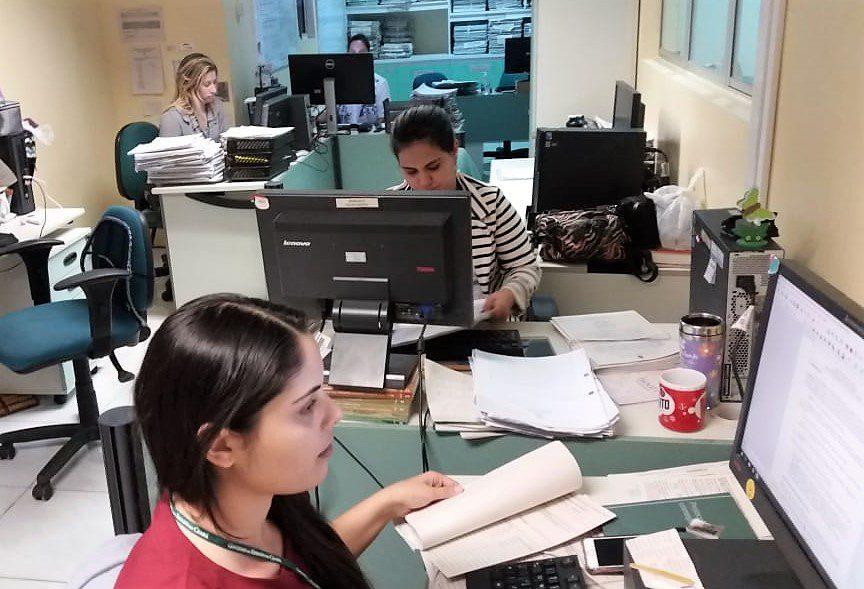 Fotografia de uma sala em tons de verde, onde estão dispostas sete mesas e cadeiras, também em verde. Sob as mesas, estão computadores e uma grande quantidade de documentos. Quatro mulheres estão sentadas em frente aos computadores, analisando as telas ou papéis