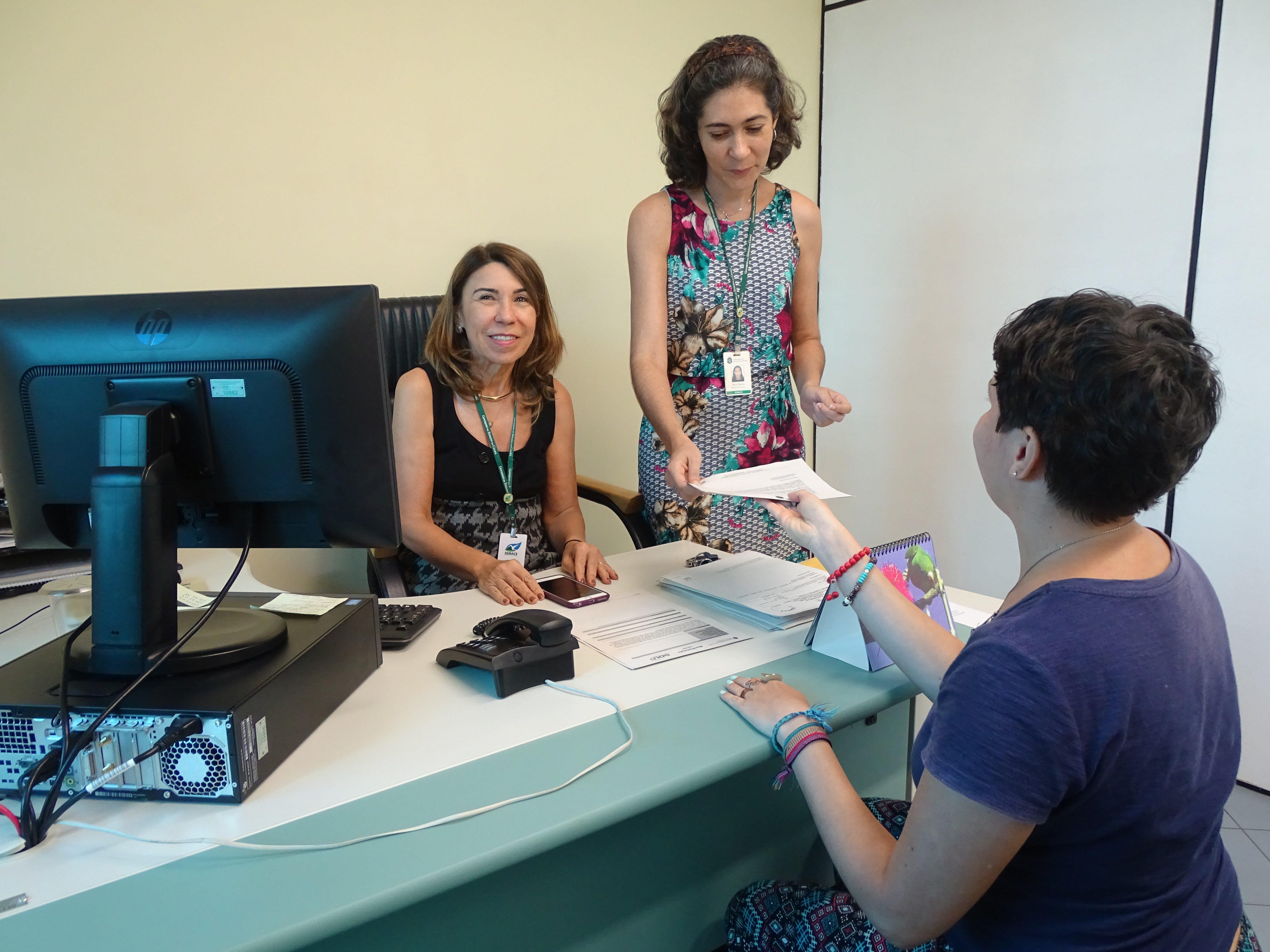 Na imagem, três mulheres estão na sala da ouvidoria da Semace. As paredes têm tons de verde. Duas estão atrás de uma mesa onde fica um computador. Uma delas entrega um papel à que está do outro lado da mesa