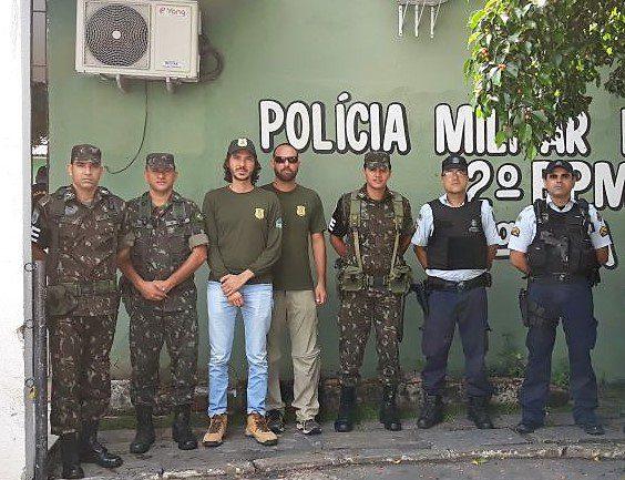 Fotografia. Sete homens, usando roupas do exército, polícia e fiscalização. Ao fundo, em uma parede verde, está escrito: Polícia Militar. 2º BPM