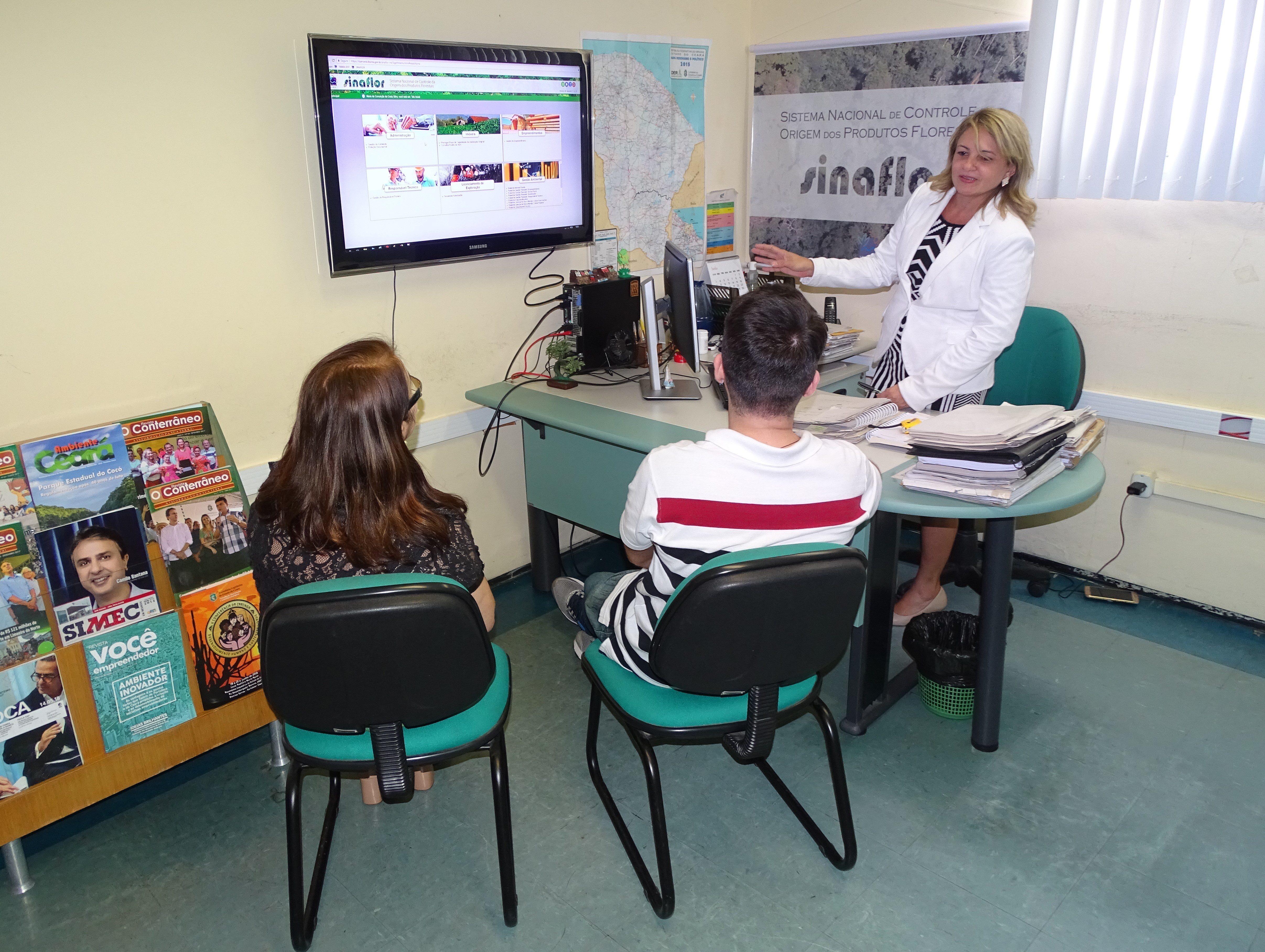 Na imagem, uma mulher aponta para uma tela onde se apresenta a plataforma virtual do Sinaflor. Ela gesticula para duas pessoas sentadas em cadeiras. Um homem e uma mulher