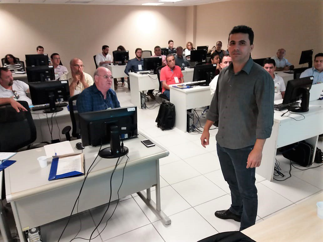 Fotografia dos participantes do Curso Sinaflor. Em primeiro plano, o professor à frente da turma olha para a câmera. Atrás dele, os mais de 20 alunos estão sentados atrás de computadores