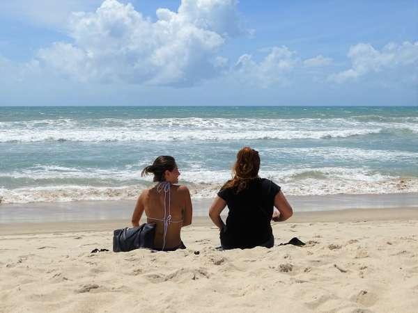 Duas mulheres sentadas na praia, de frente para o mar
