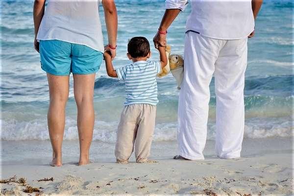 Pais e filho pequeno na praia observam o mar