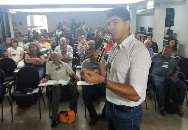 Em primeiro plano, palestrante falando ao microfone. Em segundo plano, alunos sentados em carteiras