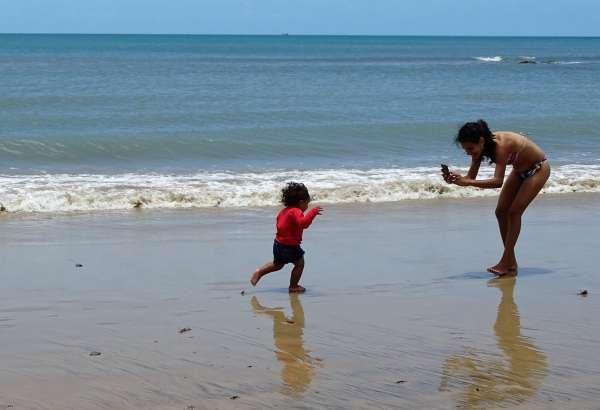 Mulher fotografando criança na praia