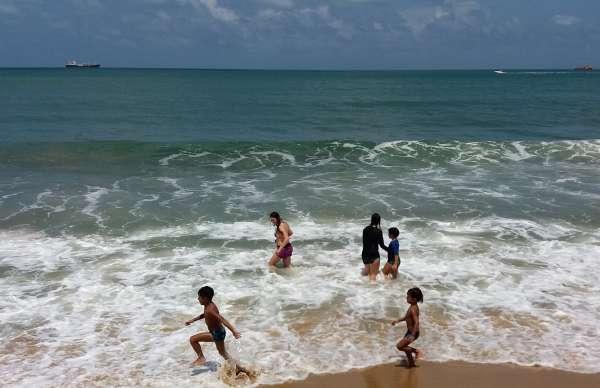 Crianças tomando banho de mar