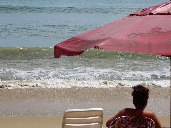 Banhista sob sobrinha contempla o mar