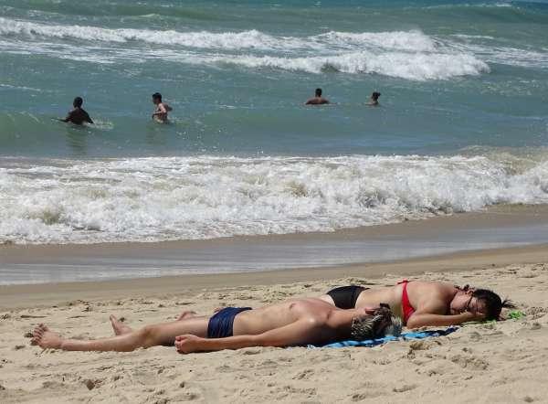 Banhistas tomam sol na areia da praias
