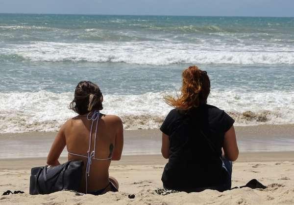 Duas banhistas na praia observam o mar