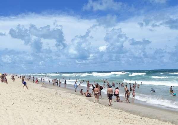 Praia com sol e banhistas