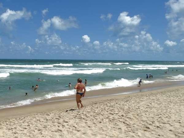 Banhista na praia caminha para o mar