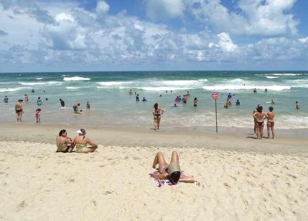 Praia com banhistas aproveitando o mar