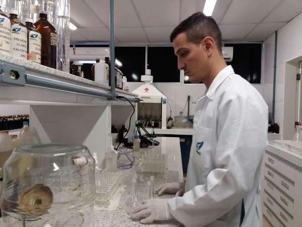 Técnico manipula vidros no laboratório de análise da balneabilidade