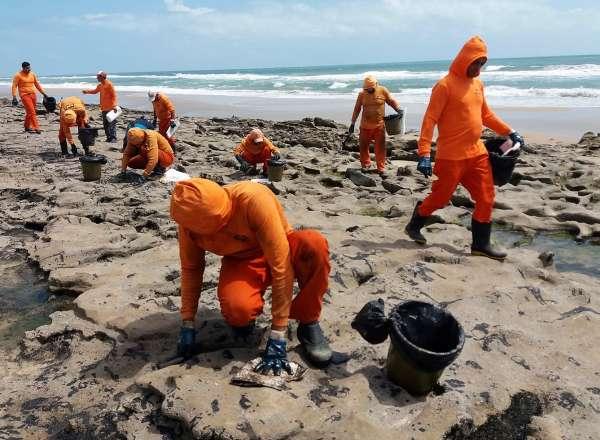 Homens removem óleo das pedras da praia de Sabiaguaba
