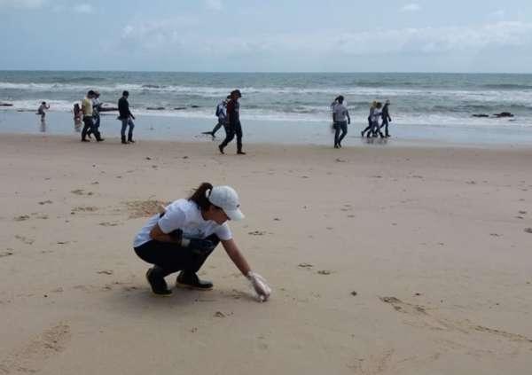 Técnica da Semace examina área da praia em busca de flocos de óleo