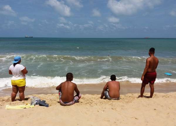 Banhistas contemplam o mar