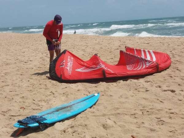 Kitesurfista ajusta vela na praia