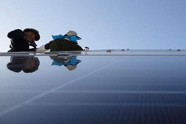 Dois homens instalam placas fotovoltaicas