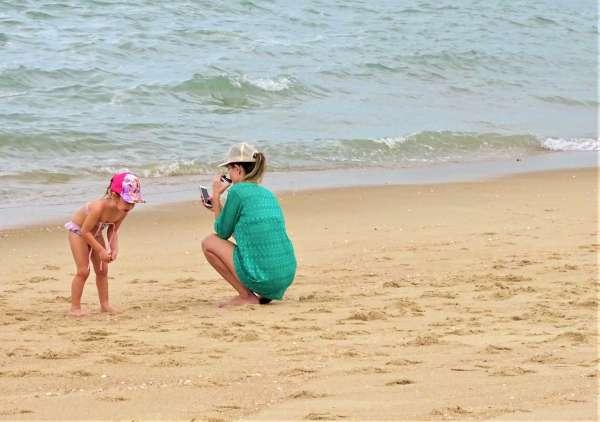 Mulher e criança brincam na areia da praia