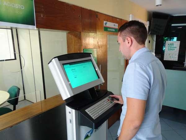 Homem consulta processo no totem do licenciamento eletrônico da Semace