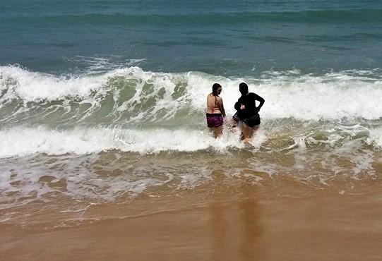 duas mulheres tomam banho de mar