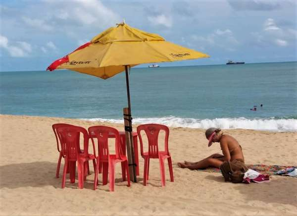 Mulher toma sol na praia do Meireles