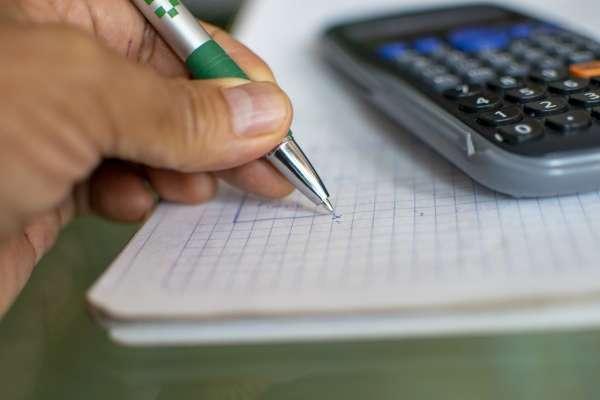 Detalhe de mão fazendo anotação em um caderno