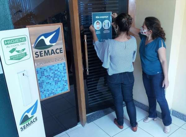 Funcionárias sinalizam prédio da Semace com cartaz
